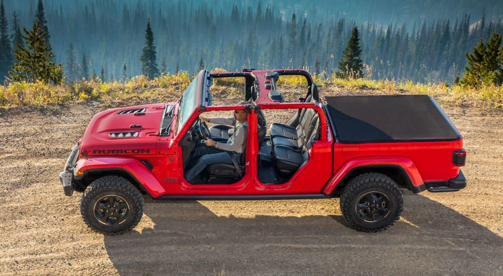 A red 2020 Jeep Gladiator is driving on a dirt, mountain road with the doors off.