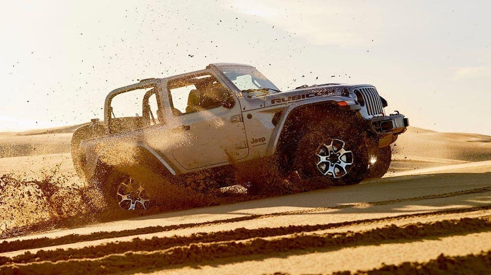 A silver 2020 Jeep Wrangler Rubicon is kicking up sand in the dunes.