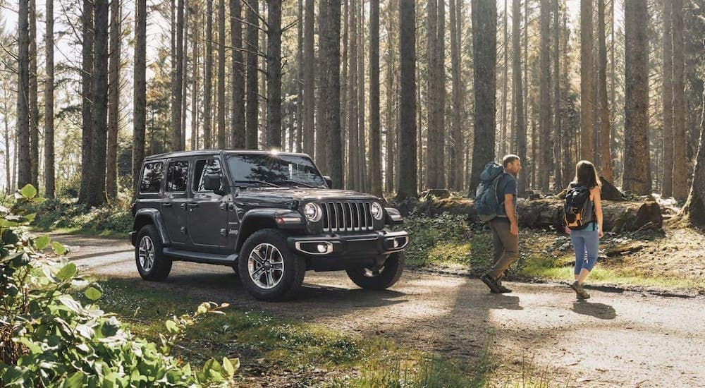 A couple walks away from their 2020 Jeep Wrangler Unlimited in a forest.