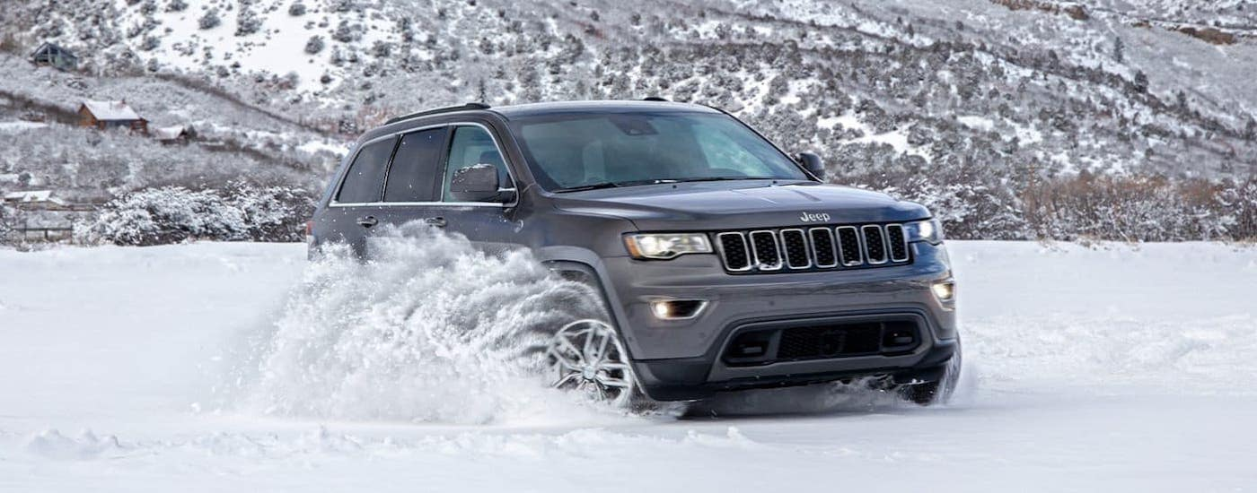A gray 2020 used Jeep Grand Cherokee is driving through snow.