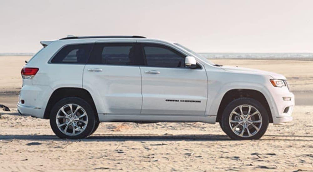 A white 2020 Jeep Grand Cherokee from a local Jeep Dealership is parked on a sandy beach.