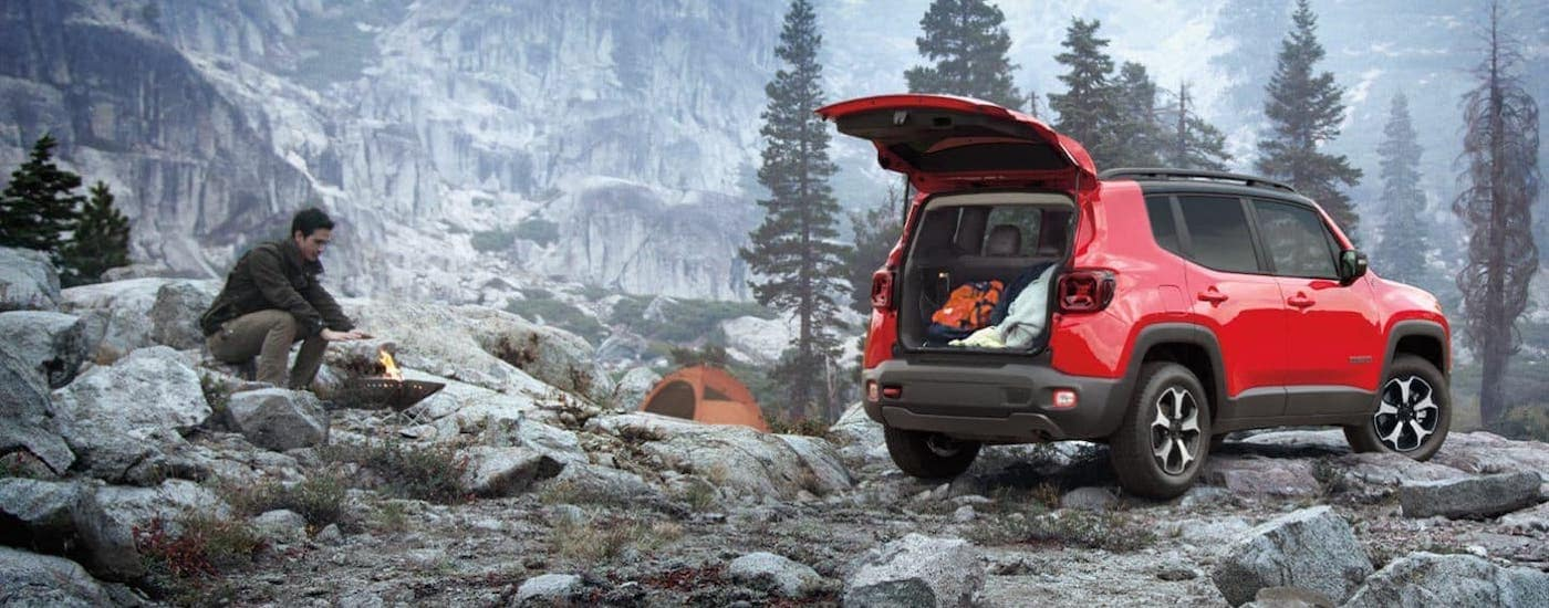 A red 2020 Jeep Renegade is parked on a rocky mountain with the liftgate open as a man makes a fire at a campsite.
