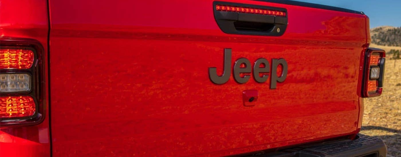 A closeup is shown of the Jeep badging on the tailgate of a red 2020 Gladiator from a Jeep dealership near me.