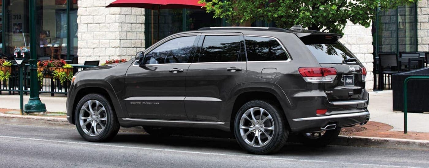 A gray 2020 Jeep Grand Cherokee is parked in front of a cafe, this model is available at a Jeep dealership near you.