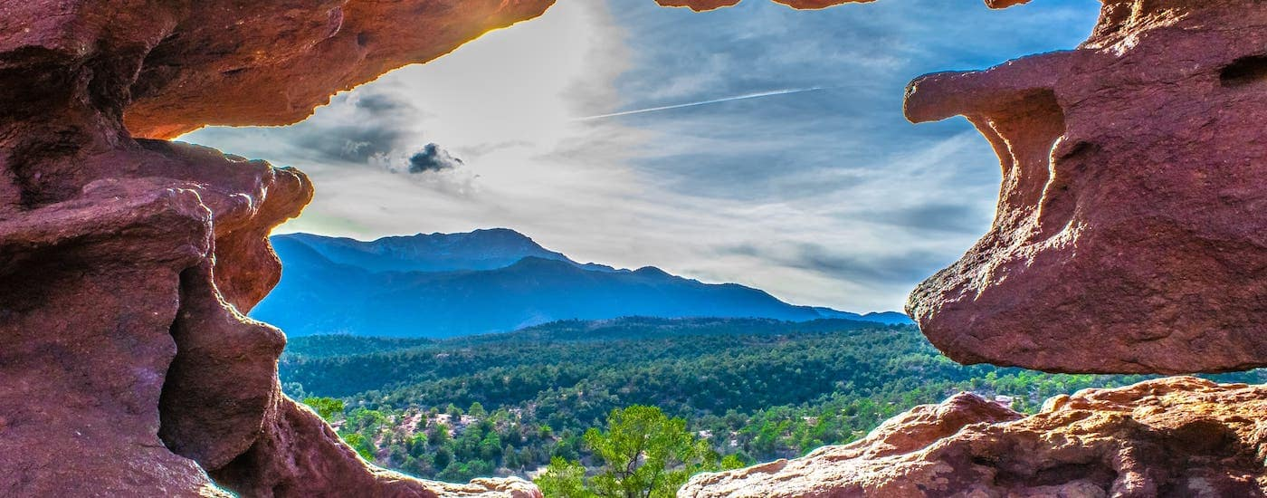 A view of the Garden of the Gods park in Colorado is framed by rocks.