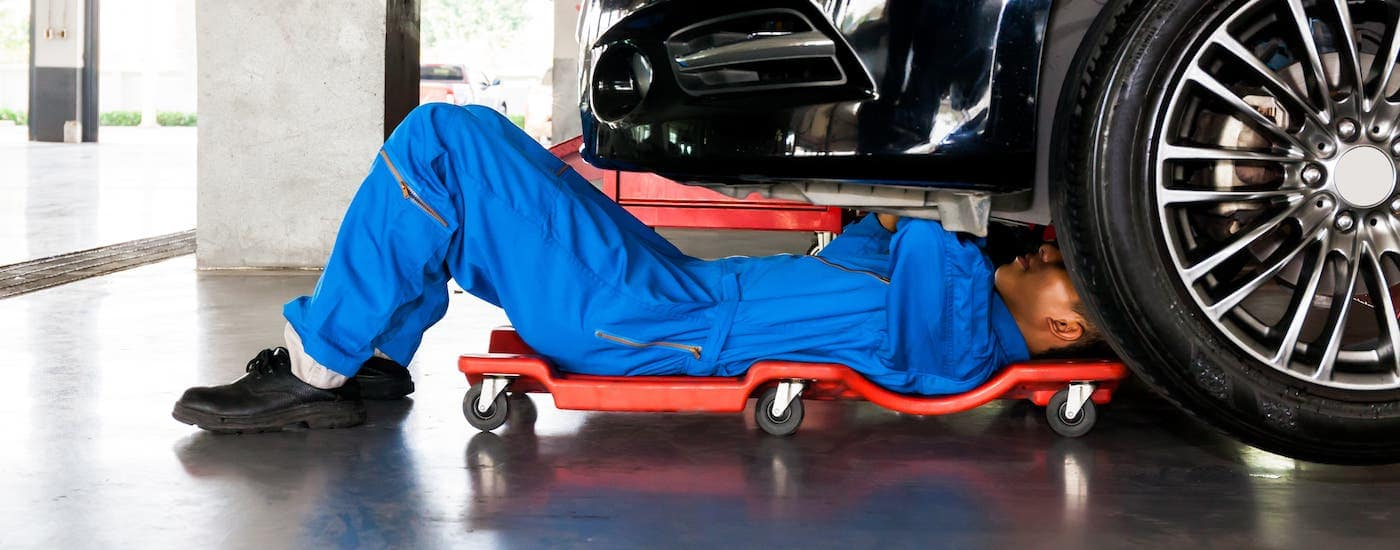 A mechanic is a blue jumpsuit is on a crawler under a car.