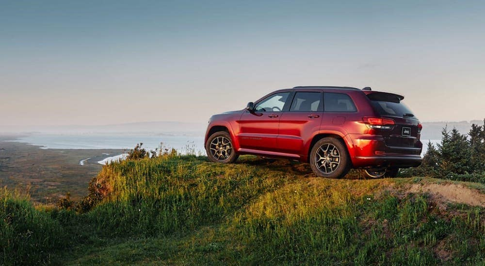 A red 2020 new Jeep Grand Cherokee is parked atop a cliff overlooking the coast.