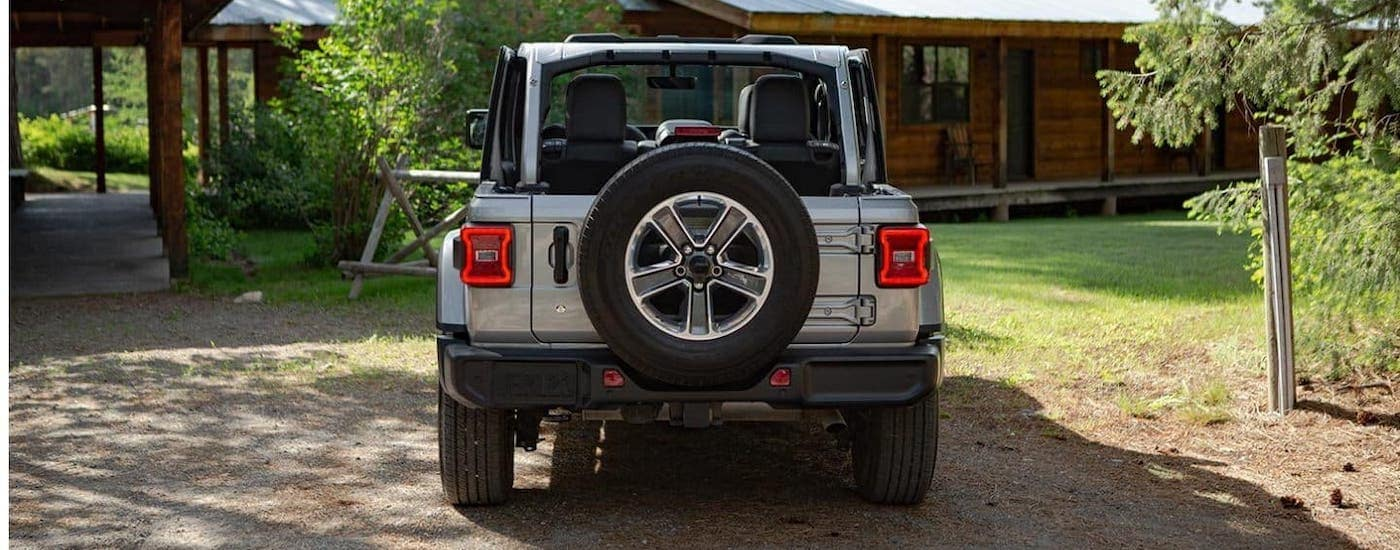 The rear is shown of a silver 2020 new Jeep Wrangler that is parked in front of a cabin near Colorado Springs, CO.