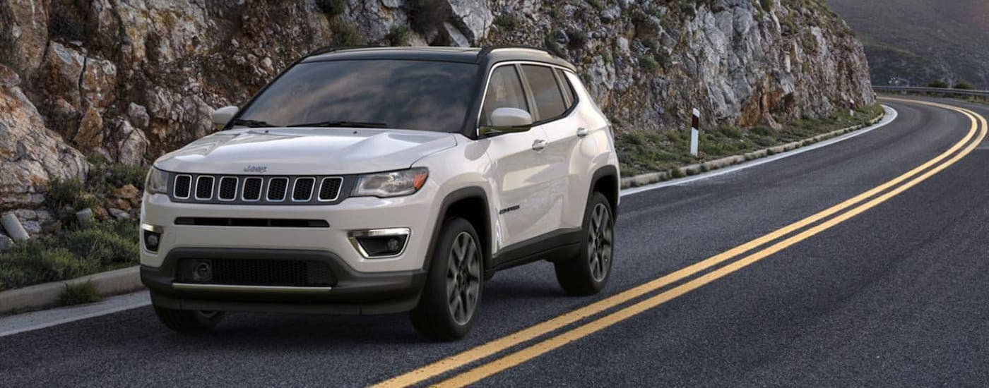 A used car in Colorado, a white 2019 Jeep Compass is driving along a rocky highway near Colorado Springs.