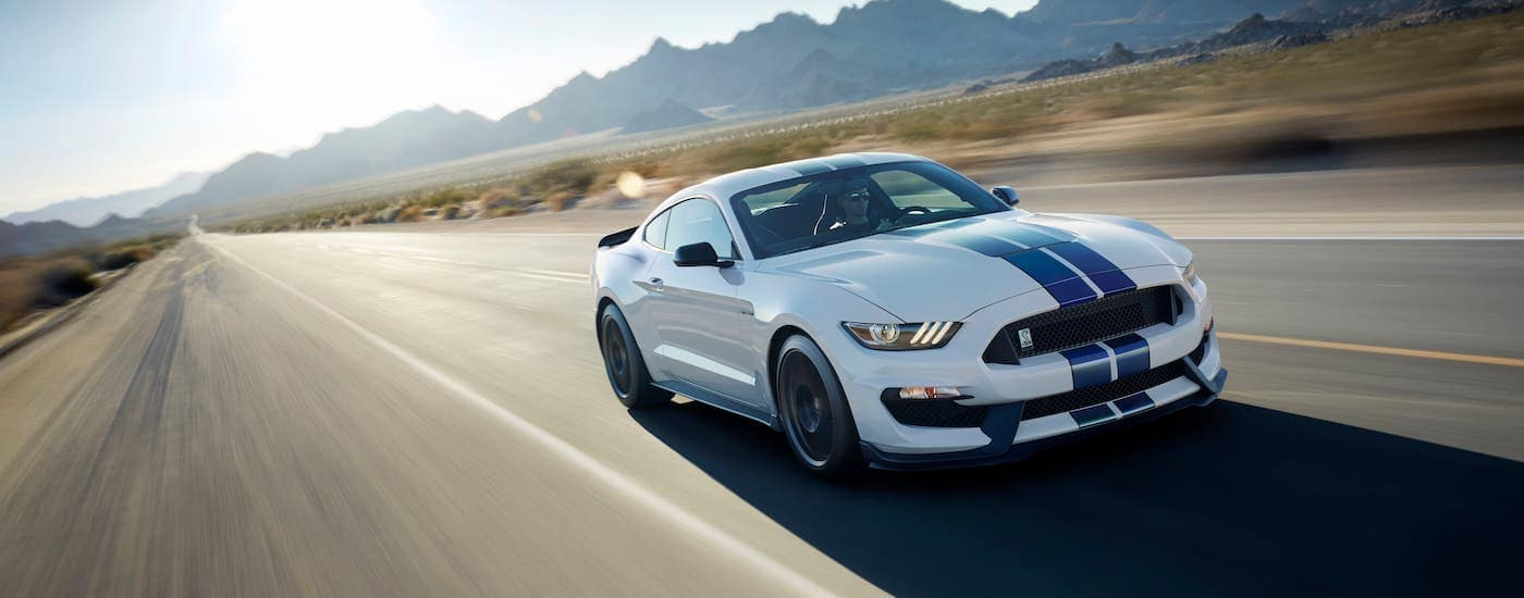 A white 2017 Ford Mustang with blue racing stripes is driving on a Colorado Springs Highway with mountains in the distance.