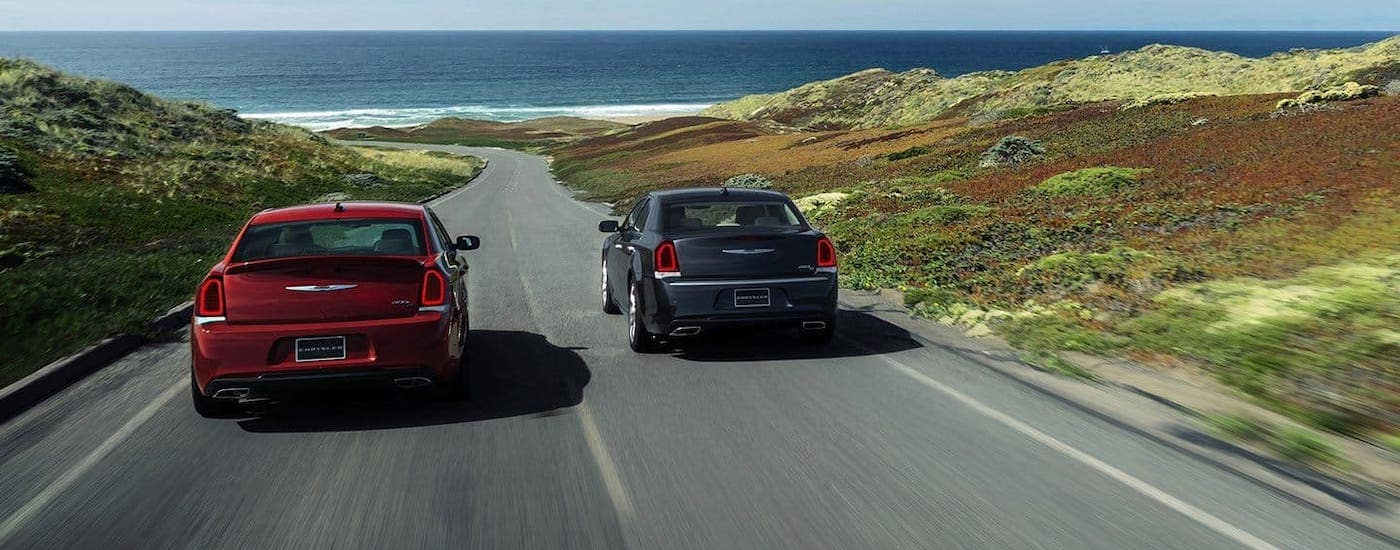 A red 2019 Chrysler 300S and a black 300C are driving towards the coast, shown from the rear.
