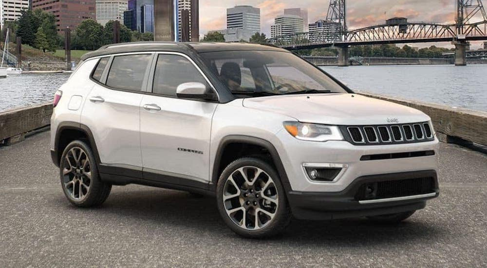 A popular used car, a white 2019 Jeep Compass is parked on a pier in front of a river.