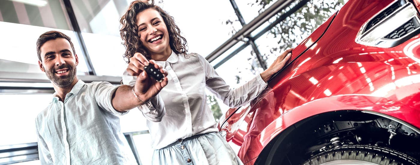 A young couple is standing in a used car showroom holding keys next to a red car.