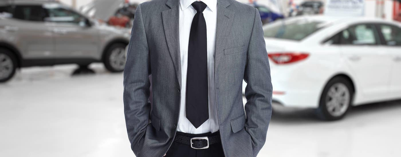 A used car salesman in a gray suit is standing in a Colorado Springs showroom.
