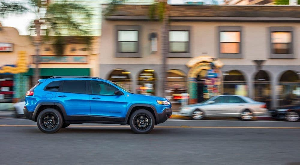 A blue 2019 used Jeep Cherokee is driving on a city street and is shown from the passenger side.