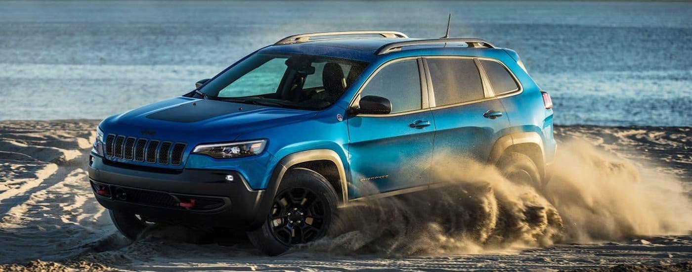 A blue 2019 used Jeep Cherokee Trailhawk is kicking up sand on a beach.
