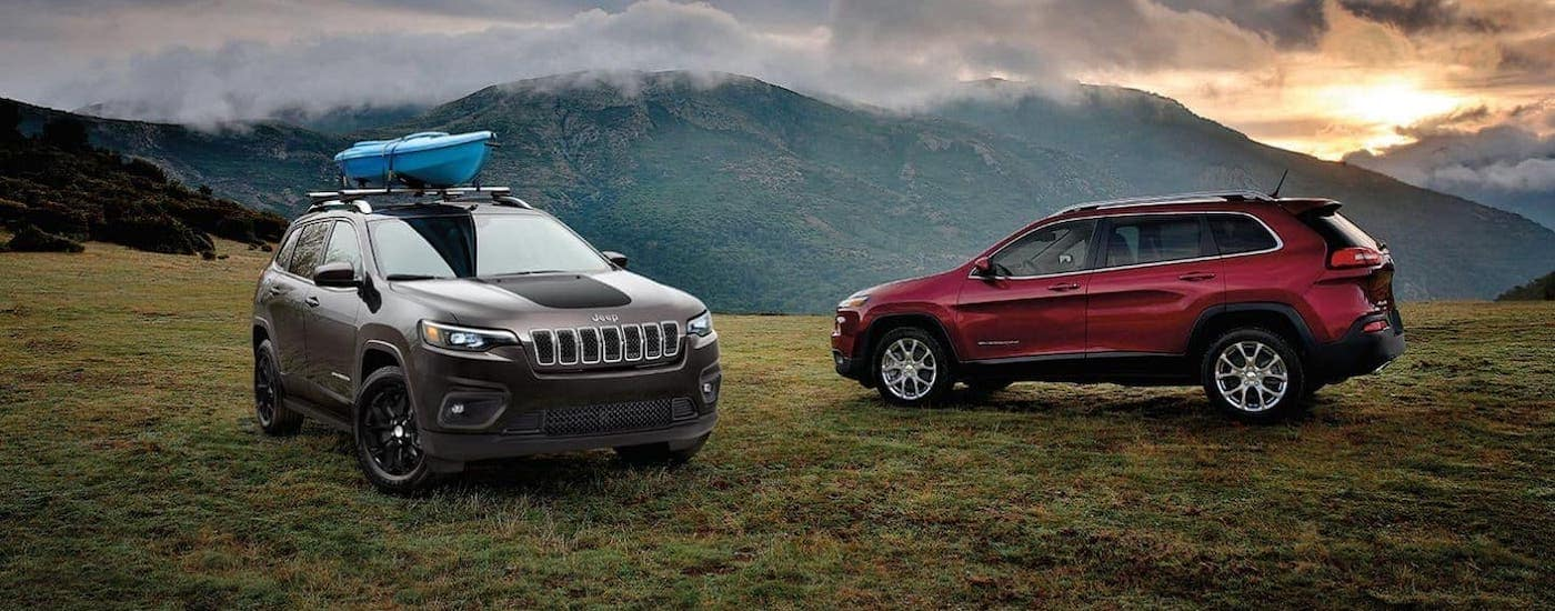 A gray and a red 2019 used Jeep Cherokee Trailhawks are parked on a mountain with clouds and mountains in the background.