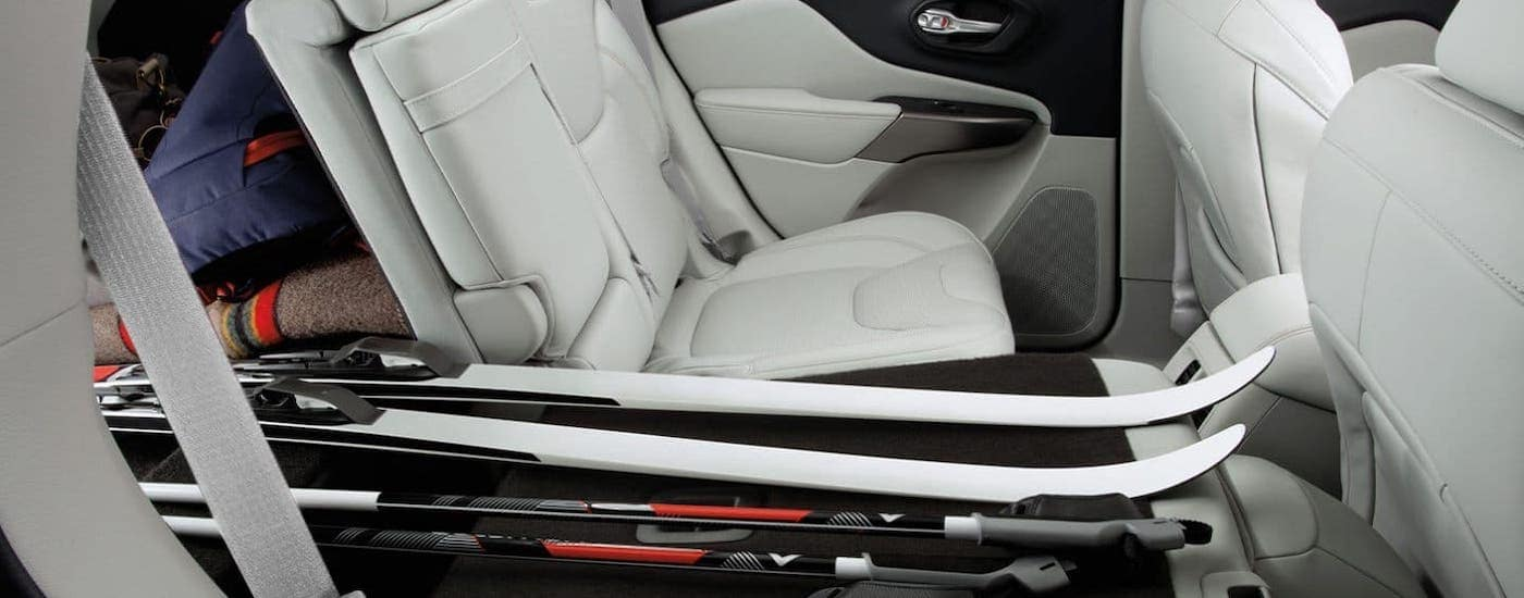 The white interior of a 2019 used Jeep Cherokee in Colorado Springs is shown with skis in the cargo area and back seat.