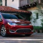A red 2018 Chrysler Pacifica is parked in front of a villa.