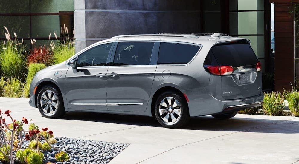 A certified pre-owned gray 2019 Chrysler Pacifica is parked in front of a home in Colorado Springs, CO.