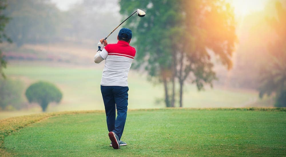 A man is shown golfing on a misty morning.