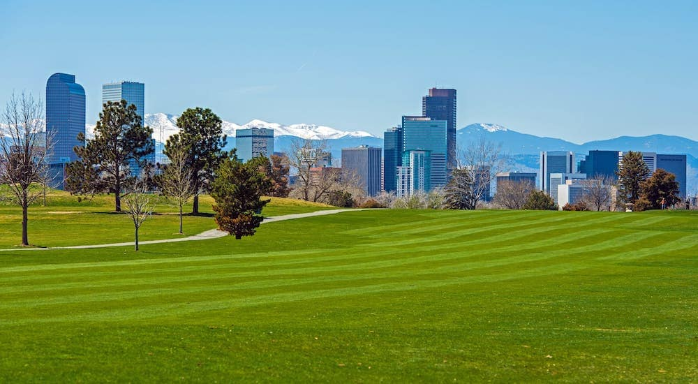 A Denver golf course is shown with mountains in the distance.