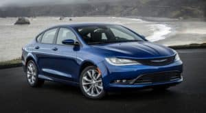 A popular used car for sale near you, a blue 2017 Chrysler 200, is shown parked in front of a beach.