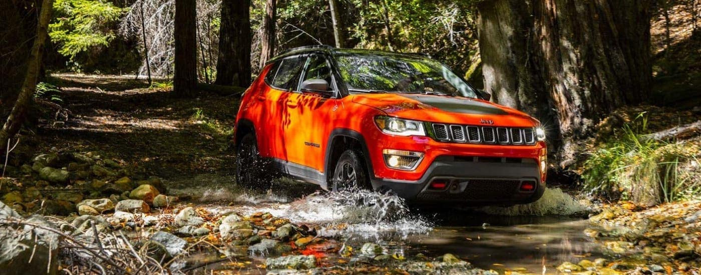 An orange 2019 Jeep Compass Trailhawk is driving through a river near Colorado Springs, CO.