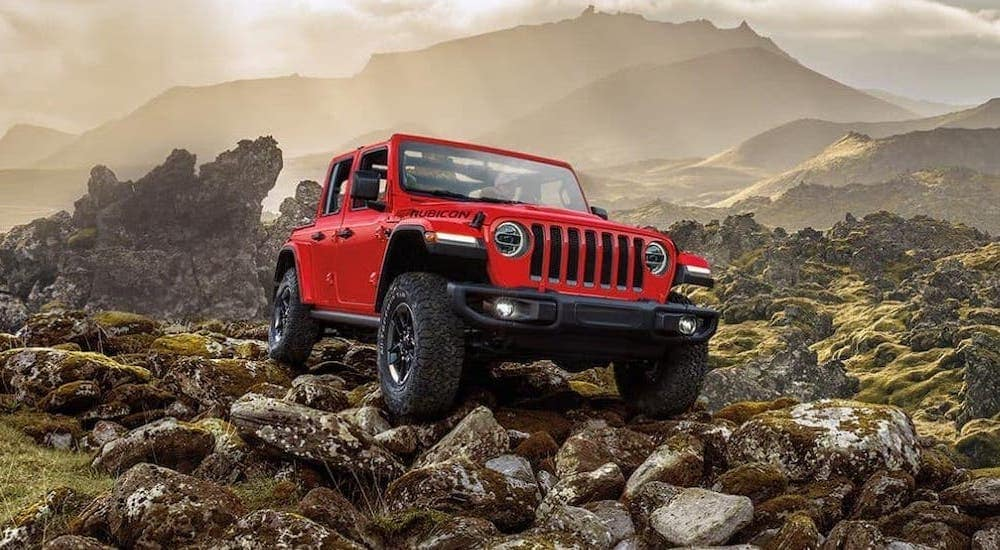 A red 2019 Jeep Wrangler Unlimited is parked on rocks with mountains in the distance.
