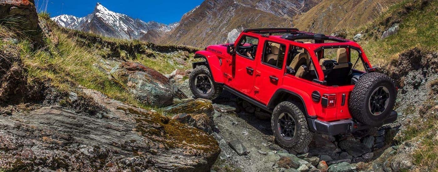 A red 2019 Jeep Wrangler Unlimited with no roof is climbing over rocks.