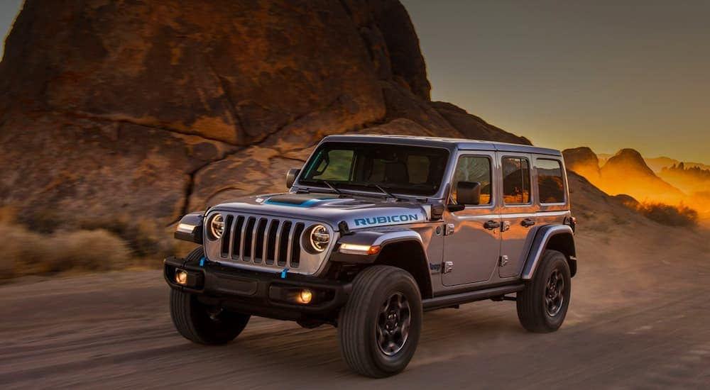 A grey 2021 Jeep Wrangler 4xe Unlimited is driving on a desert road at sunset.