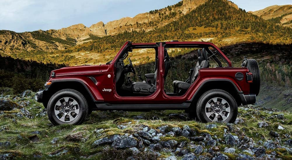 A burgundy 2021 Jeep Wrangler Unlimited is shown from the side in front of hills.