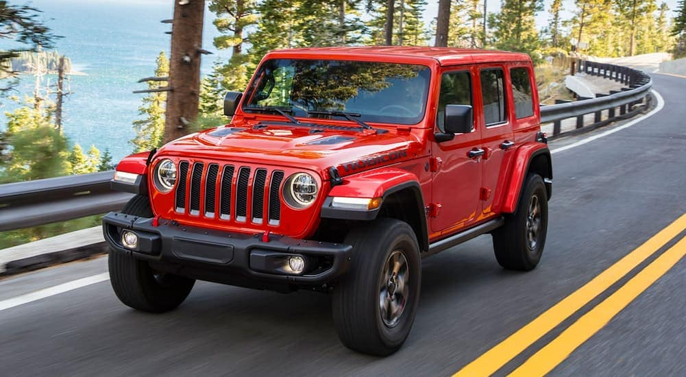 A red 2021 Jeep Wrangler Unlimited is driving past trees with a view after leaving a Jeep dealership in Colorado Springs.