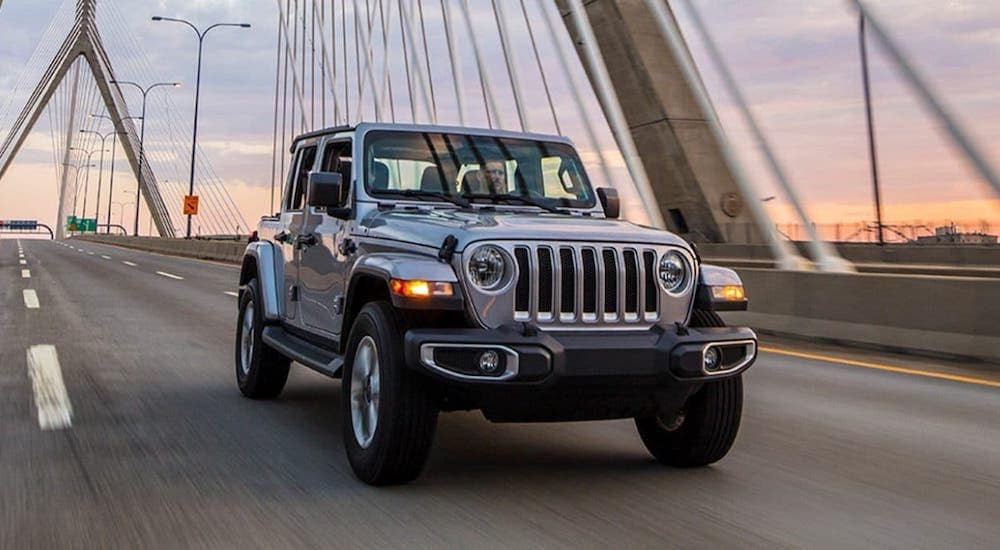 A silver 2021 Jeep Wrangler Unlimited from a Jeep dealership in Colorado Springs is driving over a suspension bridge.