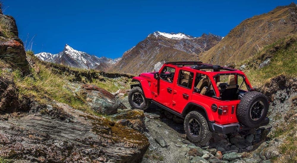 A red 2021 Jeep Wrangler Unlimited with no roof is climbing up rocks on a mountain.