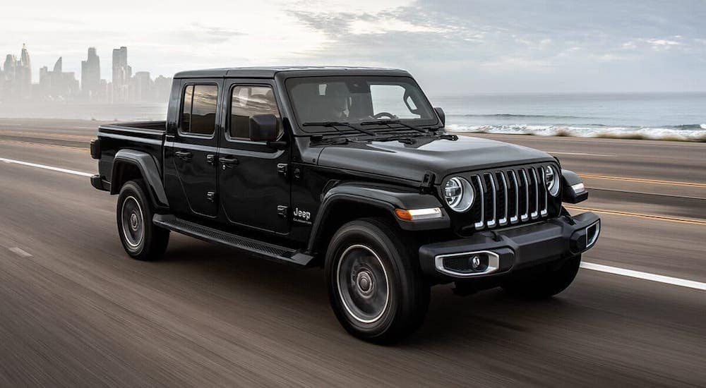 A black 2021 Jeep Gladiator is driving away from a city.