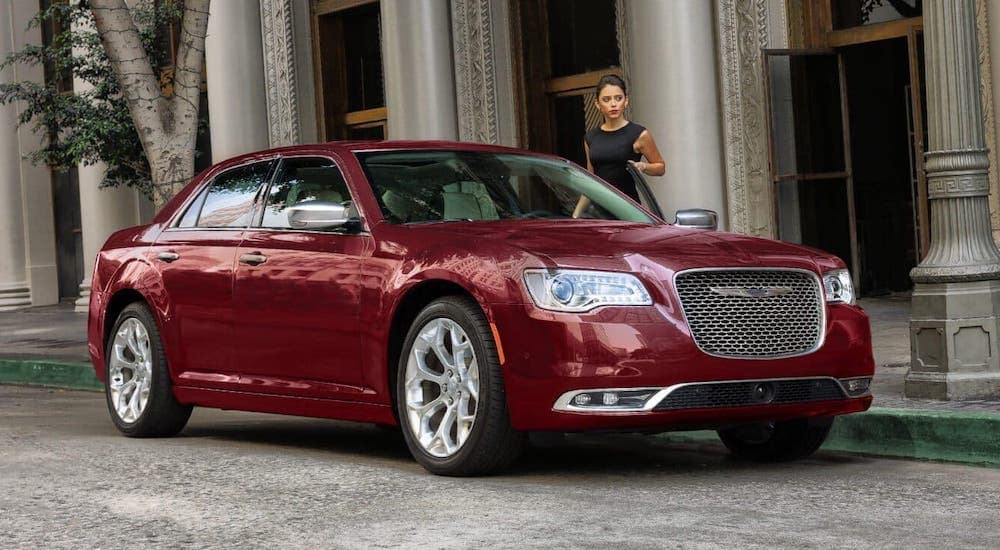 A woman is about to get into a red 2018 Chrysler 300.