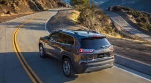 A gray 2019 Jeep Cherokee is driving around a winding road in Colorado Springs.