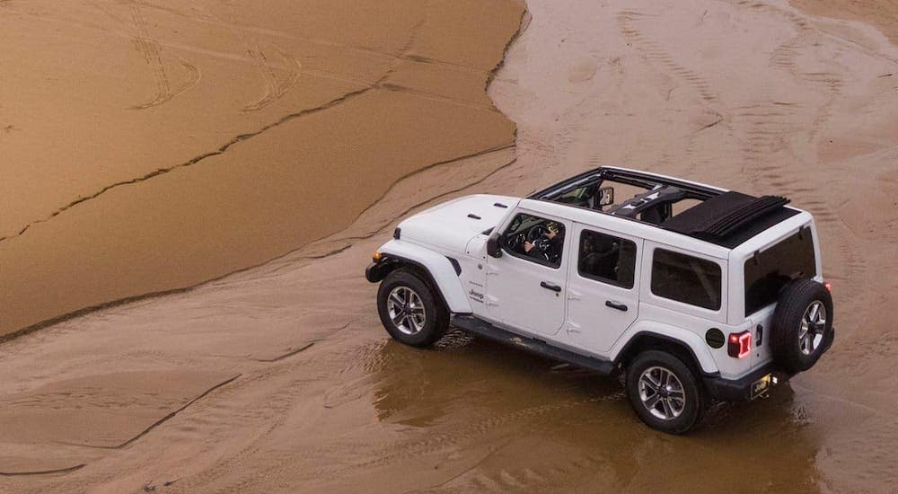 A popular used car for sale near you, a white 2019 Jeep Wrangler, is driving on a beach and shown from above.
