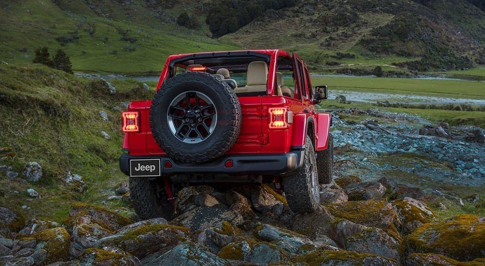 A red 2021 Jeep Wrangler is shown from the rear climbing over rocks after leaving a Jeep dealership near you.