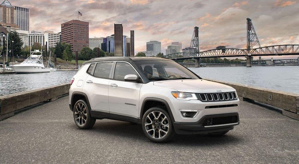 A white 2010 used Jeep Compass is parked on a pier in front of a river and city.