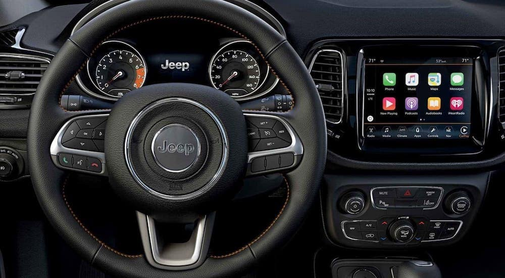 A closeup shows the steering wheel and infotainment center on a used Jeep Compass.