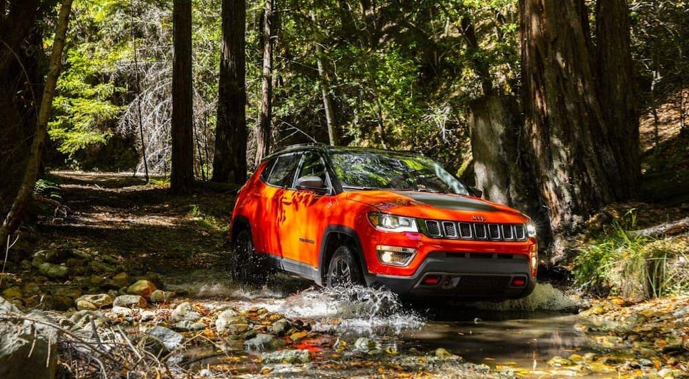 An orange 2019 used Jeep Compass Trailhawk is driving through a river in the woods near Colorado Springs, CO.