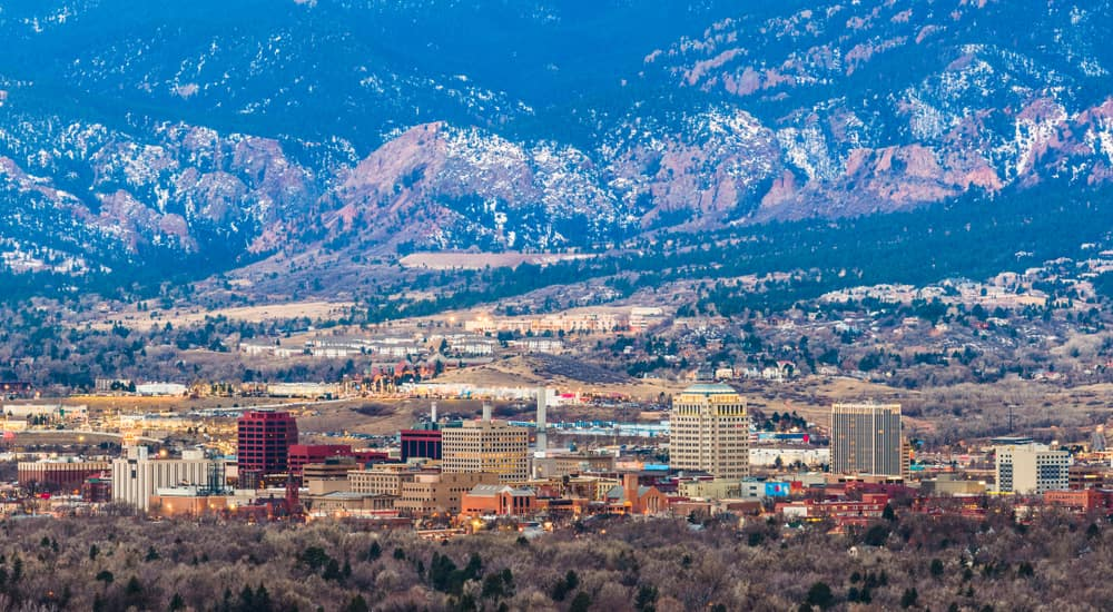 Aerial view of tall Colorado Springs buildings in front of tall mountains