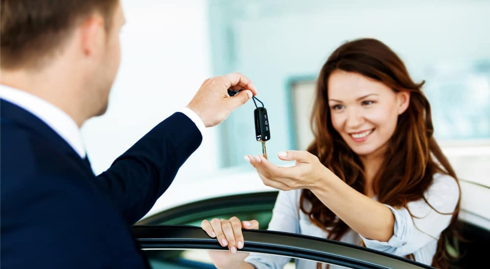 Woman in a blue shirt standing behind an open car door, reaching out to grab a car key from a man in a suit