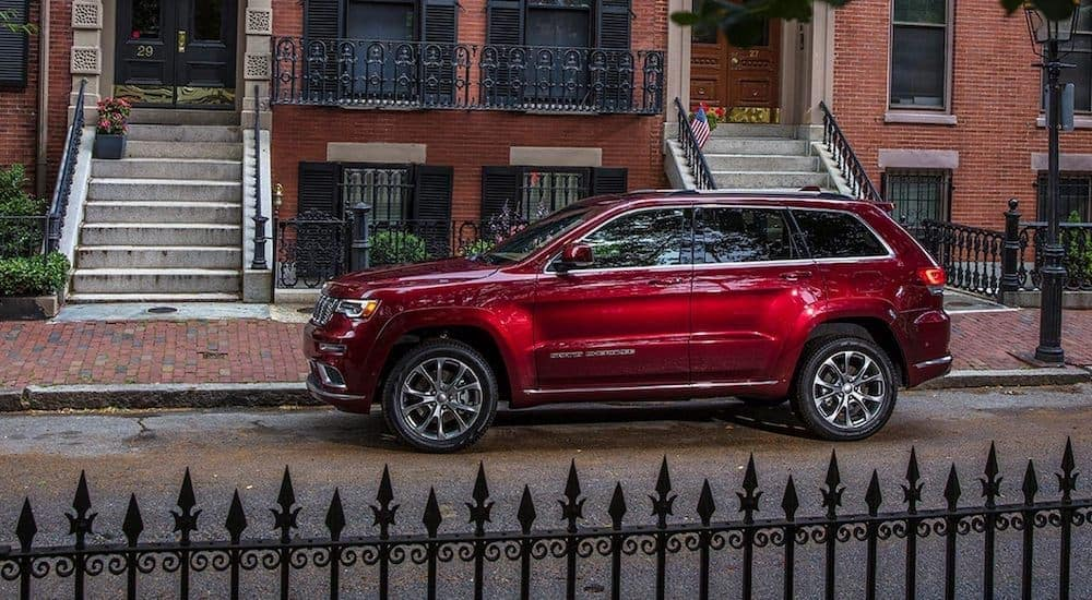 A red 2021 Jeep Grand Cherokee Summit is parked on the street behind a wrought iron fence.