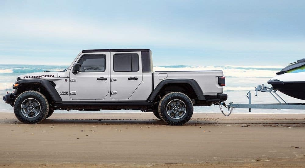 A white 2021 Jeep Gladiator Rubicon is towing a boat on the beach.