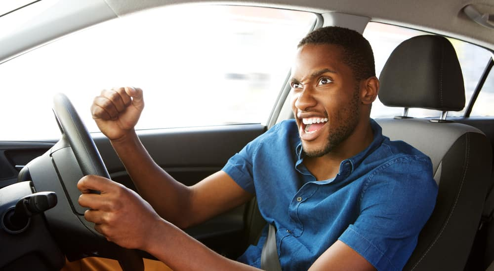 Man in a blue shirt sitting in the driver's seat of a vehicle pumping his arms in excitement