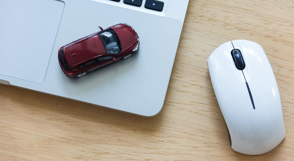 Red toy car sitting next to the trackpad on a silver laptop sitting on brown table next to a wireless mouse