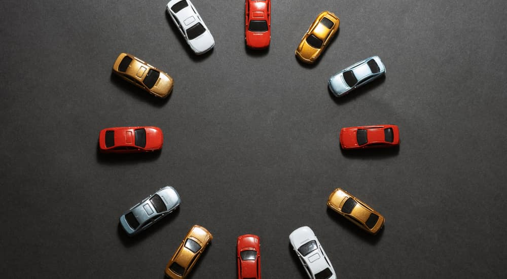 Twelve red, gold, blue, and white toy cars in a circle with the fronts facing in